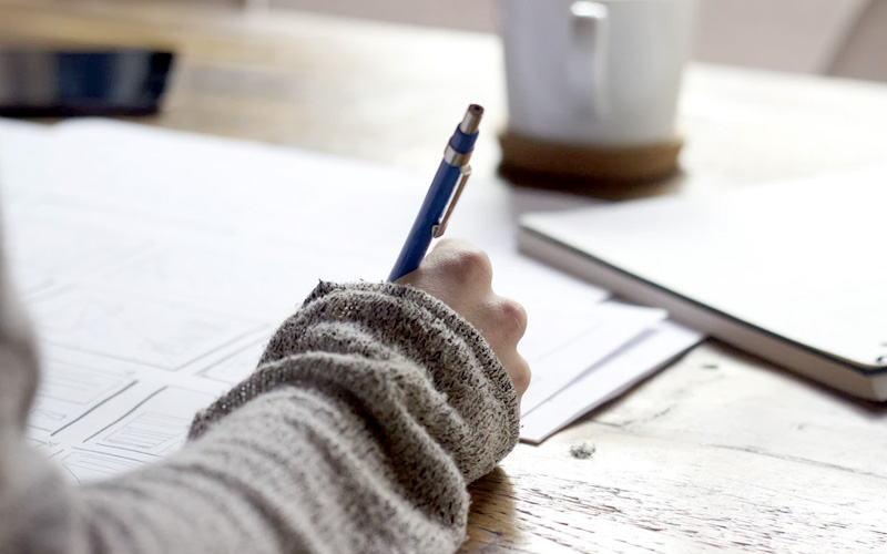 A student with a long-sleeved jumper on takes notes with a pen