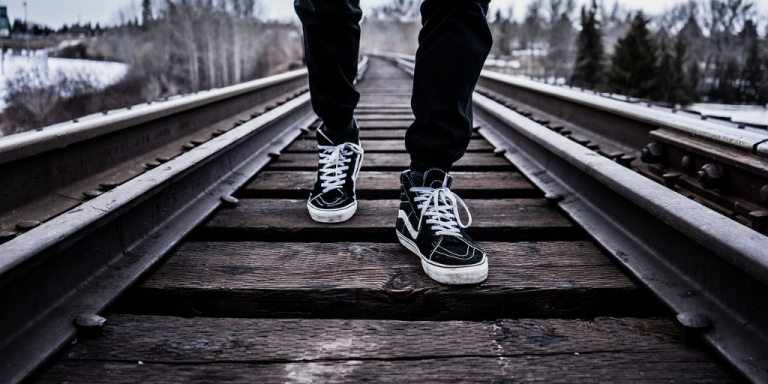 Youth walking on railway line