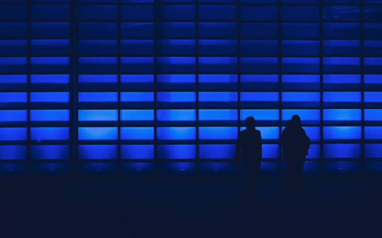 Two people silhoutted against an abstract blue screen with many blocks, representing patterns and data