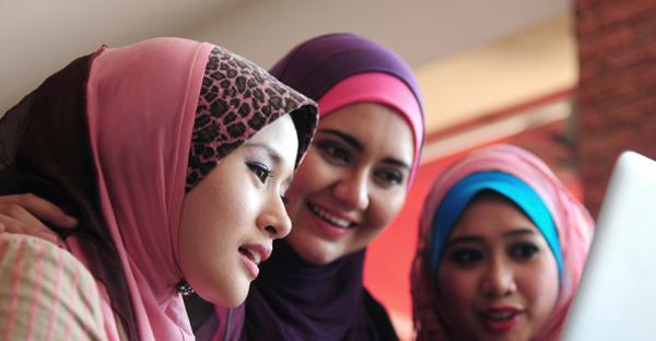 Three muslim girls around a laptop