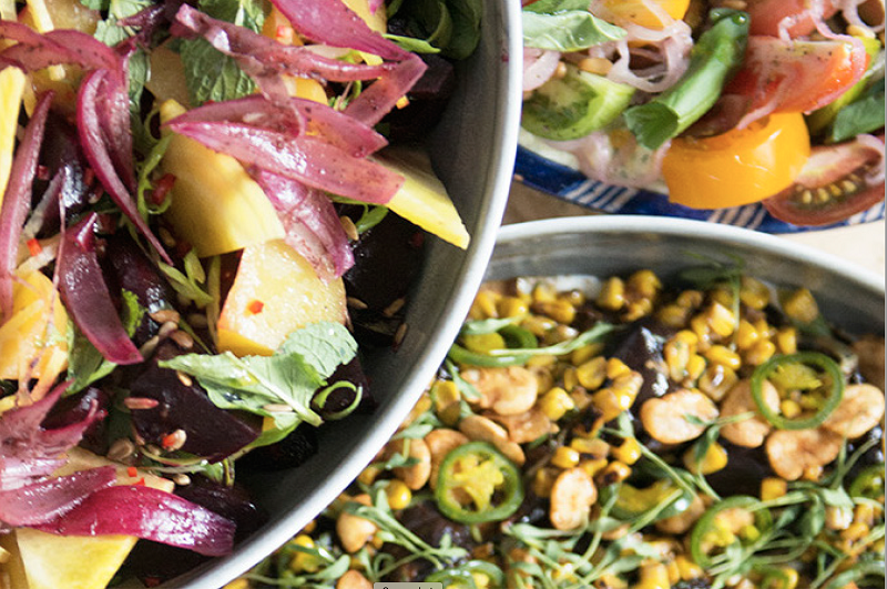A close up photo of plant-based food arranged in two bowls and a plate which overlap in the top right hand corner