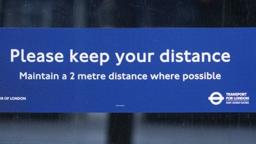 A blue Covid-19 sign urging social distancing in the London underground