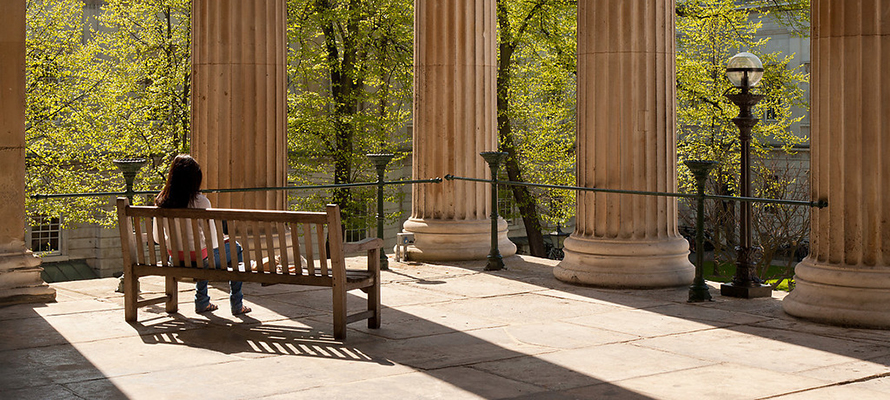 student-on-bench-by-portico-columns