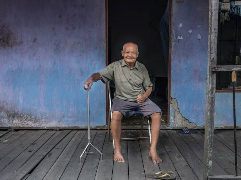 An older man sitting on a chair in front of a house.