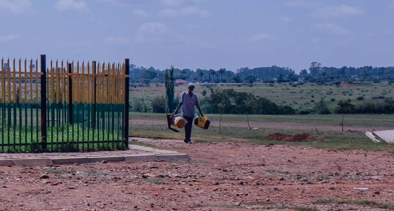 Image of a black person carrying two large items in either hand while walking in an open space.