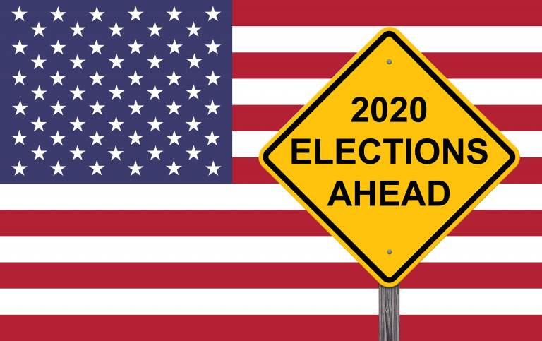 A road sign with the words '2020 Elections Ahead' in front of an American flag