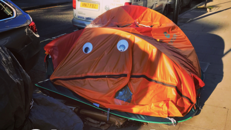 orange tent with smiley face stuck on