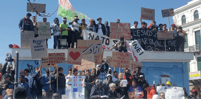 An image of a group of people holding up signs about immigration