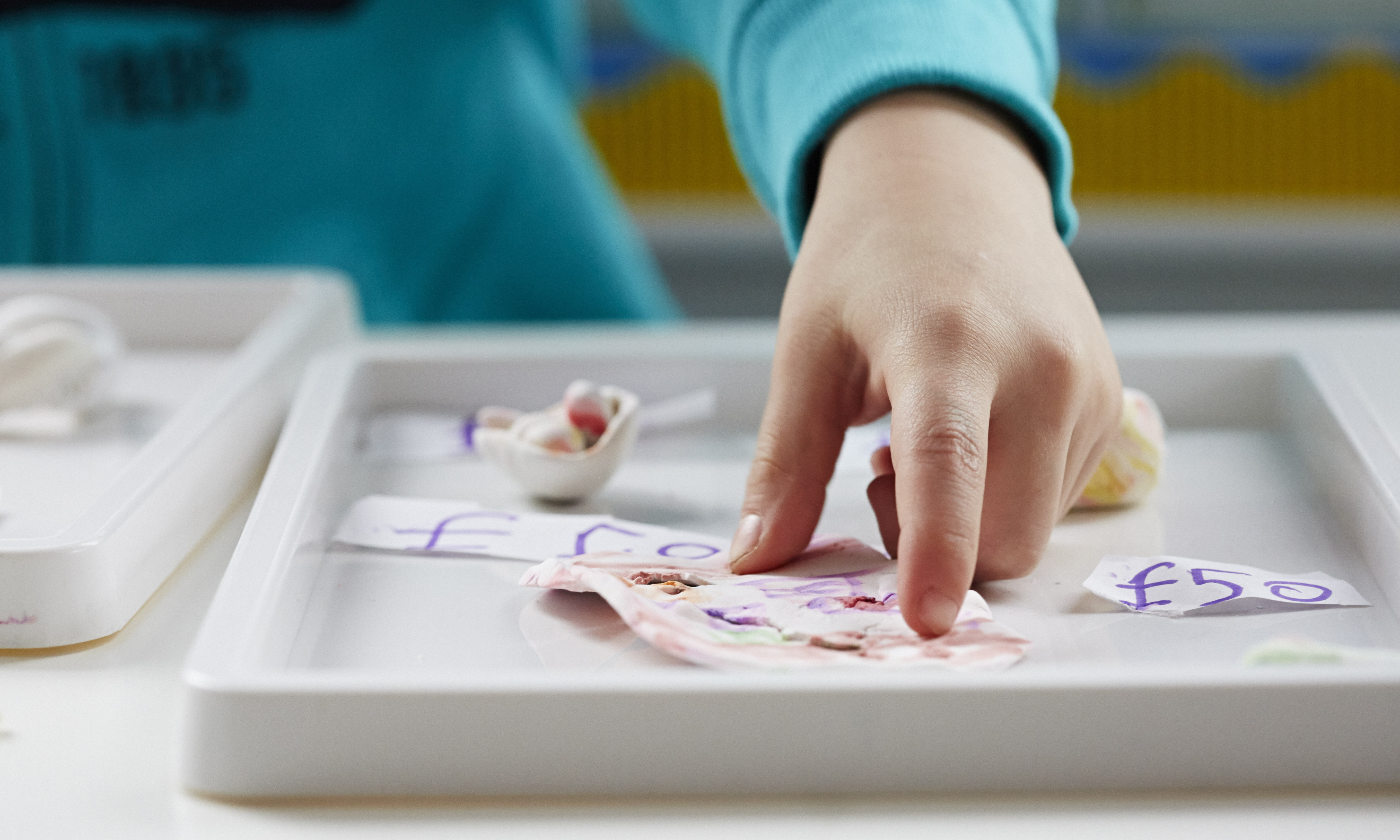 Image of child's hand moving paper
