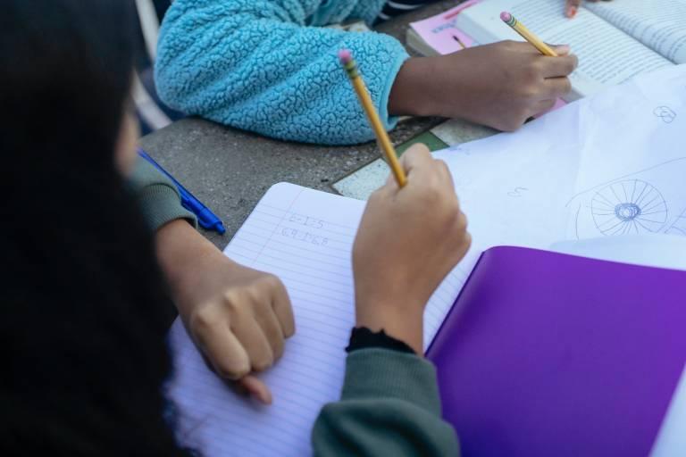 Hands of two children doing school work