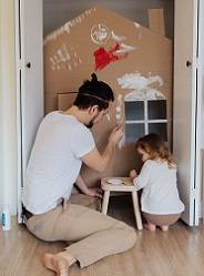 Photo of man and toddler painting a cardboard house