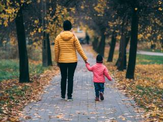 Woman and child walking through a park