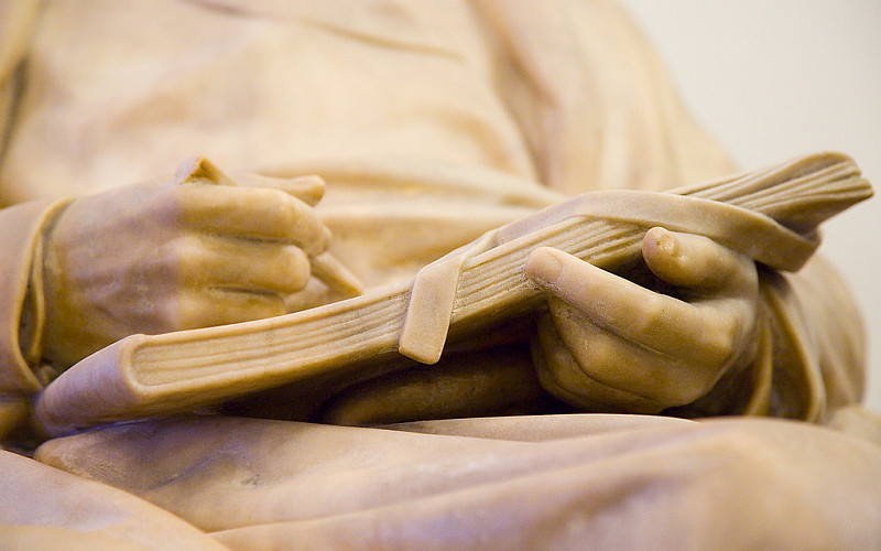 Portion of a statue with book in hands