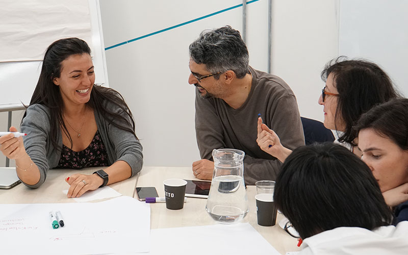 a group of people sitting around a table laughing