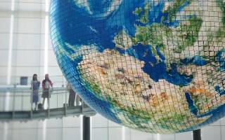 Two girls looking at large globe