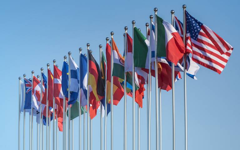 row of various world flags on poles