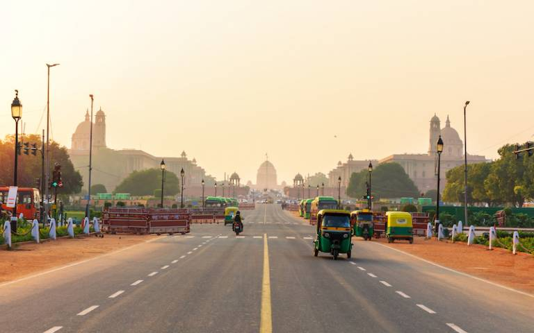 sunset traffic in New Delhi, tuc tuc cars on the road to the Presidential Residance.