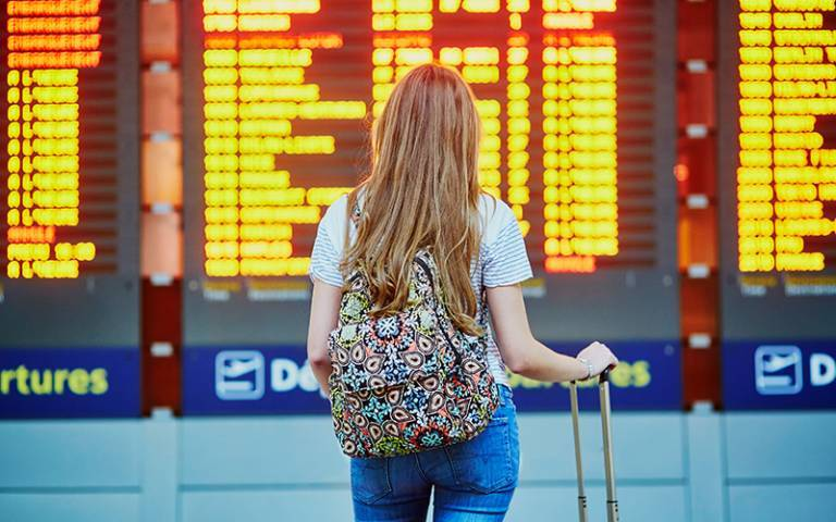 female student standing in front of departures board at airport