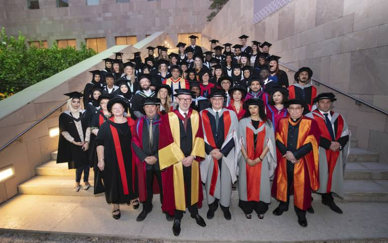 UCL Qatar graduates on steps in their caps and gowns