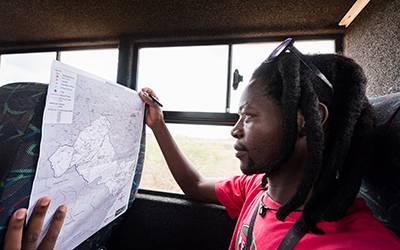 Jabulani Sibiya studies a map of households that make up the Africa Health Research Institute's population research area. Image: Ben Gilbert, Wellcome…