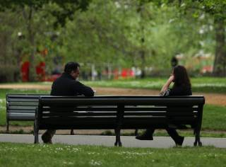 Image of people sitting on a bench in a park