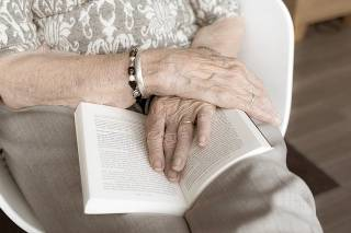 hands resting on open book