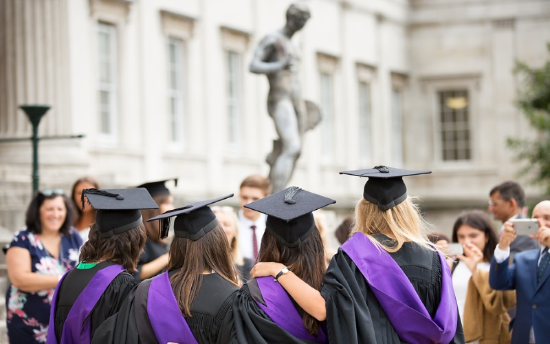 Image of UCL students graduating in black and purple robes and cap in front of monument near school