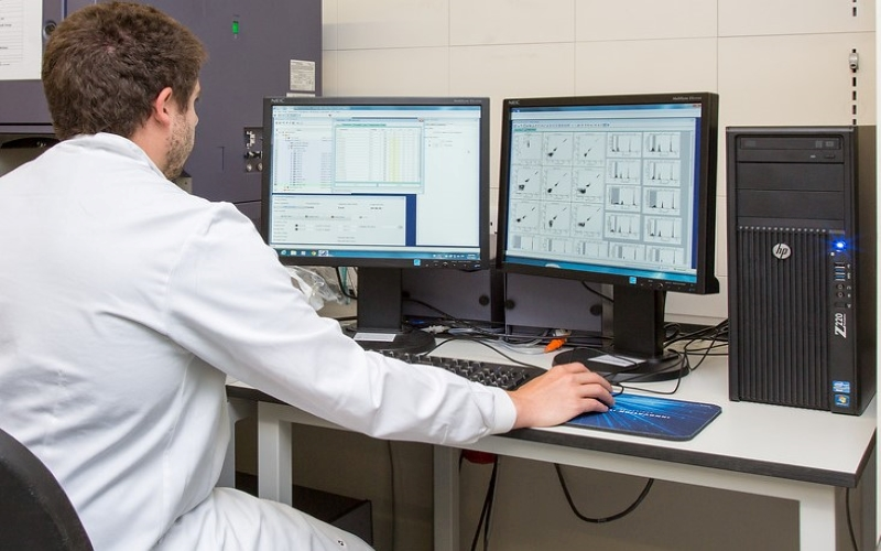 person researching in front of two screens with science