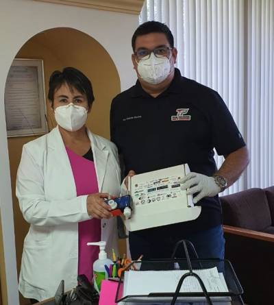 A Baja Ventura member (right) delivers a device to the Director of ISSTECALI