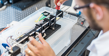 A researcher works on electronic equipment