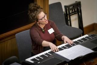 Rachel Weston playing a keyboard and singing