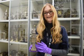 photo of Jemima Jarmon holding Jewish artifact in front of a cabinet of artifacts at a museum