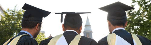 Three UCL graduates in cap and gown from behind