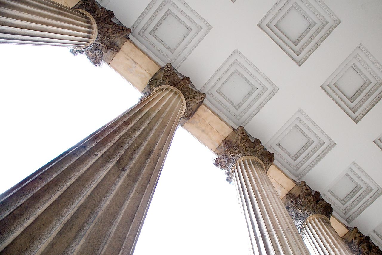 View from below of the pillars on the UCL portico and a stonework ceiling