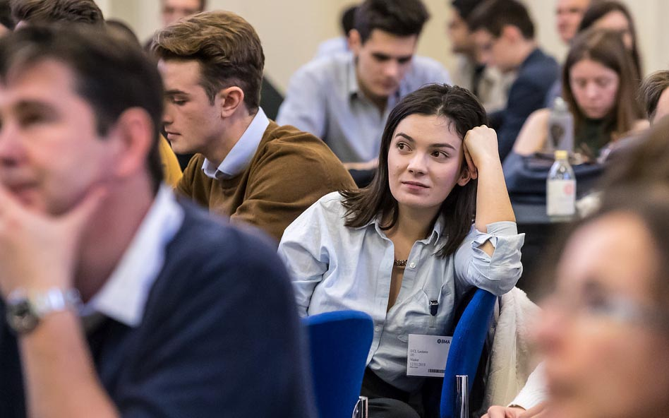 A young woman in a lecture theatre surrounded by other students