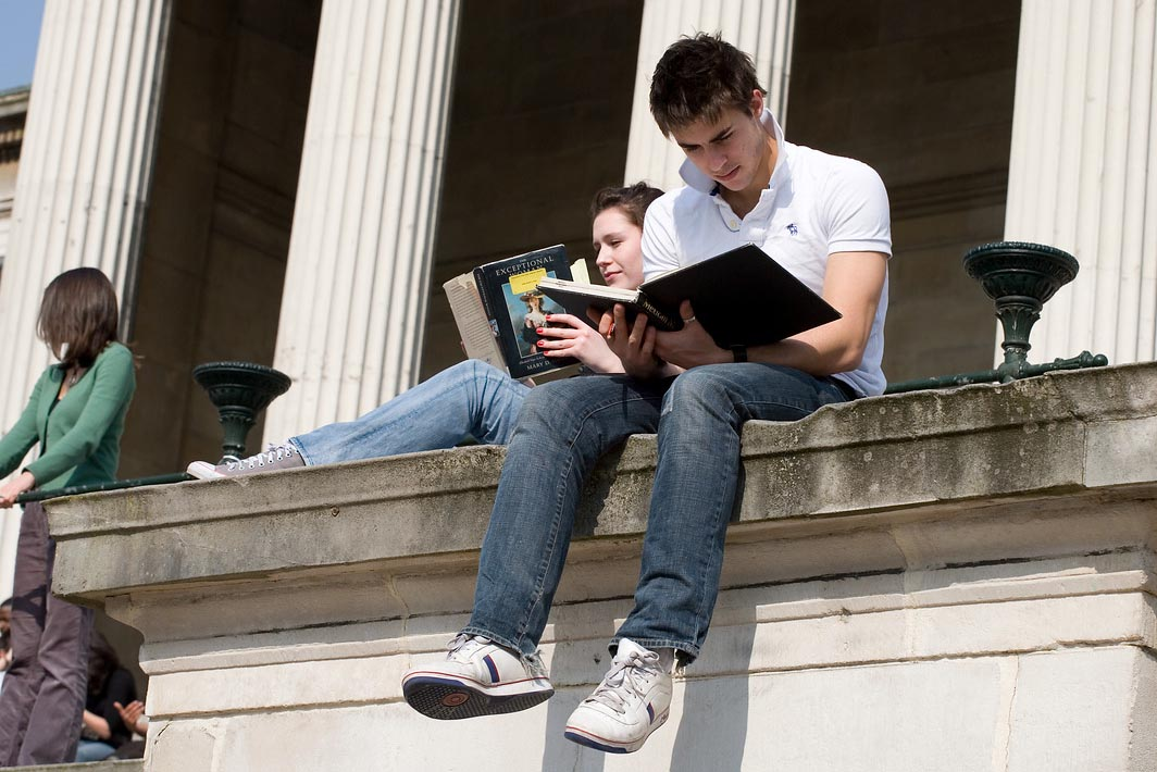 A young man sat on a the steps outside UCL, reading a book