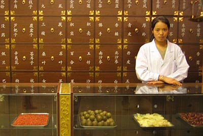 A young woman at the counter of a Chinese medicine shop
