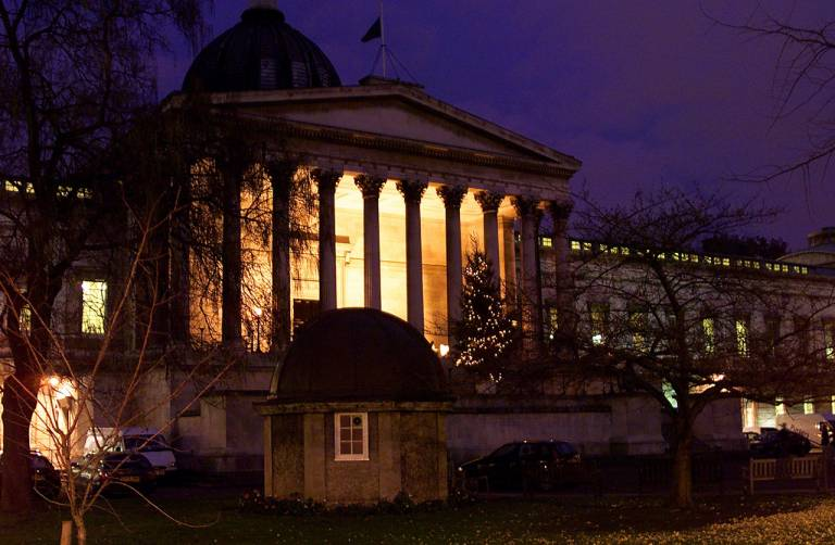 View of the UCL main building at nighttime with a decorated Christmas tree standing on the portico