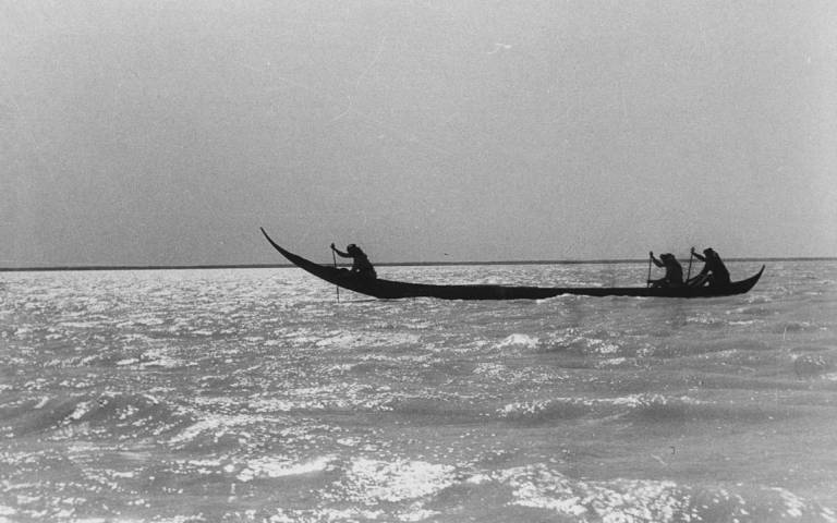 Black-and-white image of the tarada canoe, manned by three oarsmen, floating on a river