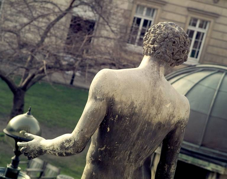 View from behind of a weathered stone statue of a man, standing in the front quad of UCL