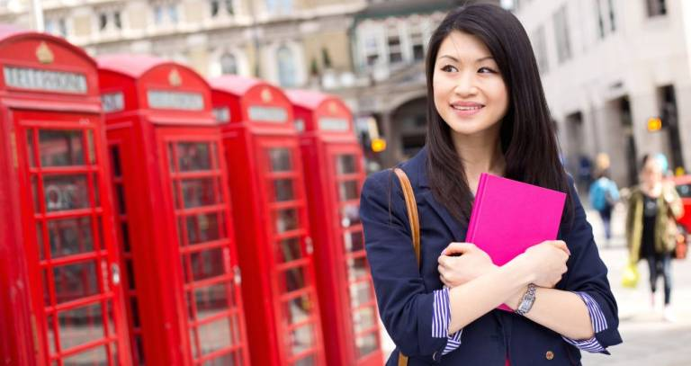 Student holding a pink notebook in front of London phoneboxes