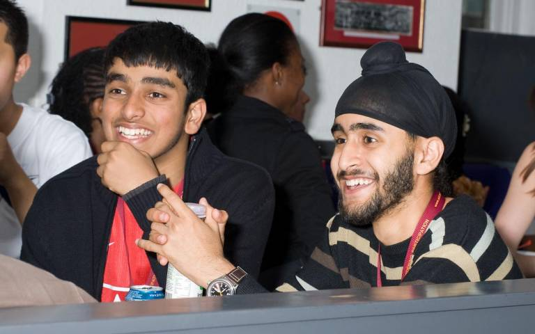 Two smiling young men participate in a pub quiz at the student bar