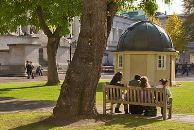 Students sitting on a bench in the UCL front quad