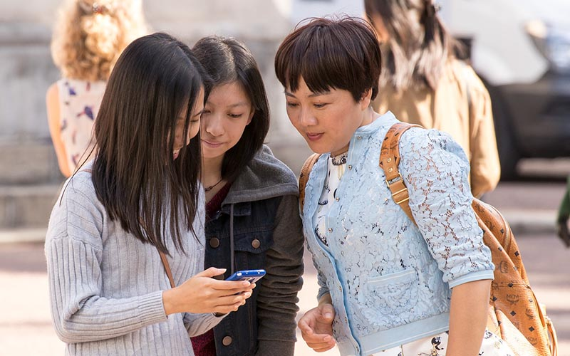 Three young women in casual clothing looking at a mobile phone