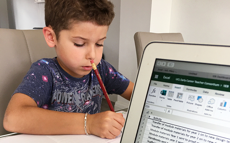 Child doing schoolwork beside a computer