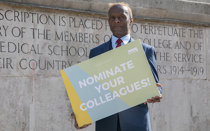 Man holding 'nominate your colleagues' sign