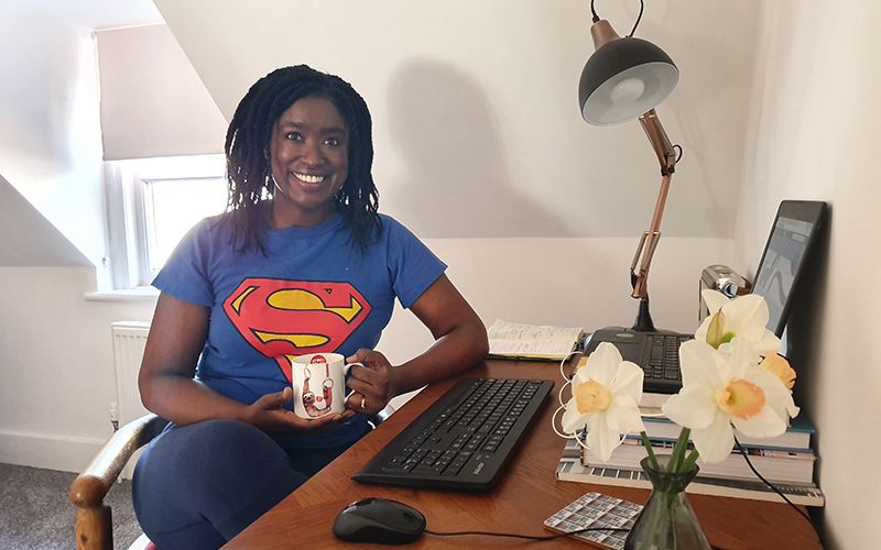 Image of a woman at home at her desk wearing a superwoman t-shirt