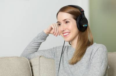 Woman listening through headphones…