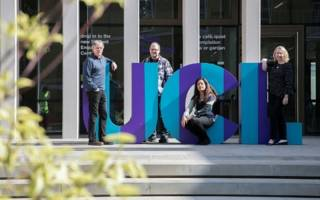 Image of people next to large UCL letters