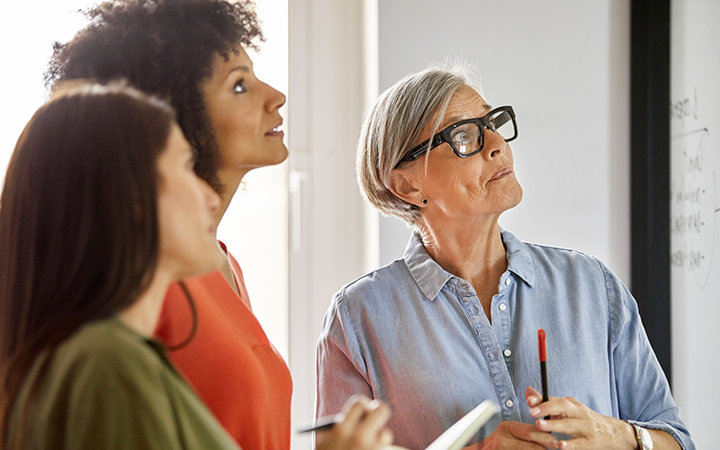 Three women looking at a whiteboard